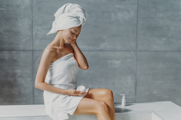 Refreshed young european female applies anti wrinkle cream, poses in bathroom, wrapped in bath towels, prevents signs of skin aging, has clean body after showering. wellness, wellbeing concept