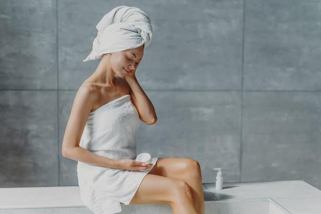 Освеженная молодая европейка наносит крем от морщин, позирует в ванной, завернувшись в банные полотенца, предотвращает признаки старения кожи, имеет чистое тело после душа. велнес, концепция благополучия