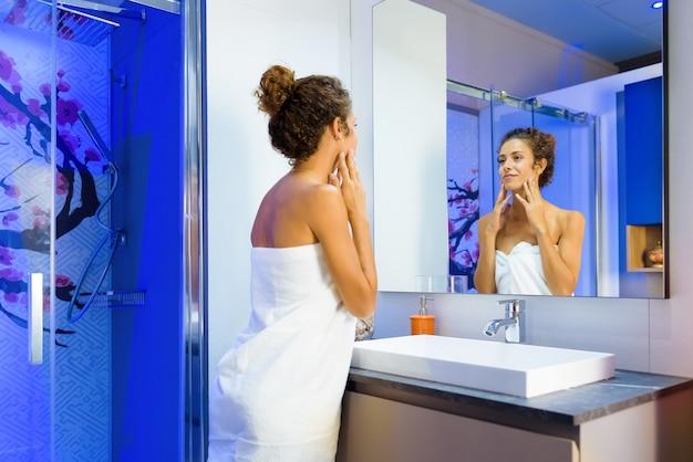 Освеженная молодая женщина, завернутая в чистое белое полотенце в ванной