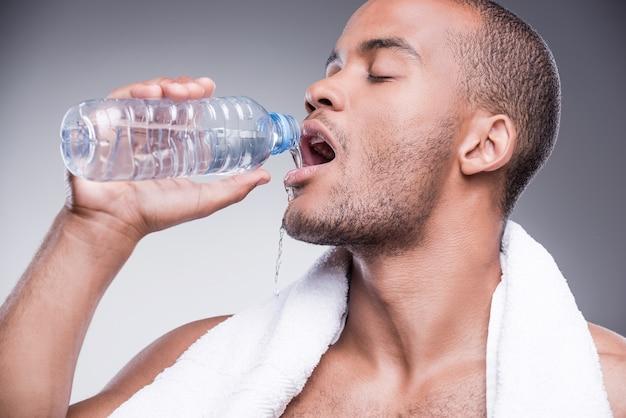 훈련 후 상쾌함. 젊은 벗은 아프리카 남자 물 병을 들고 웃 고