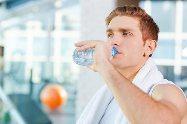 Освежение после тренировки. усталый молодой человек с полотенцем на плечах и питьевой водой, стоя в тренажерном зале