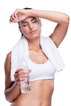 운동 후 상쾌함. 흰색으로 격리된 채 물병을 들고 손으로 이마를 만지는 피곤한 젊은 여성