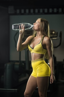 Refreshing after a workout. beautiful woman drinking water in gym