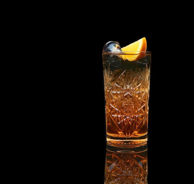 검은 배경에 얼음과 감귤류와 상쾌한 알콜 칵테일