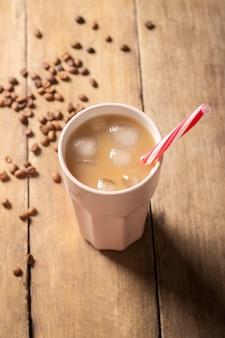 木の表面のグラスにアイスコーヒーを入れてさわやかにします。渇きを癒すコンセプトのコーヒーショップ、夏。フラット横たわっていた、トップビュー