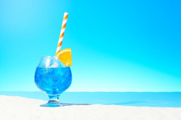 모래 해안에 있는 유리잔에 얼음과 오렌지 한 조각을 곁들인 상쾌한 파란색 음료