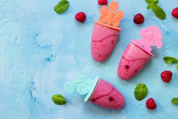파란색 콘크리트에 상쾌한 어린이 아이스크림 아이스 캔디 라즈베리 셔벗