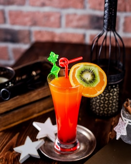 Refreshing cocktail decorated with orange and kiwi slices