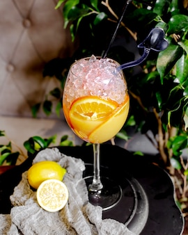 Refreshing cocktail with crushed ice and slices of orange