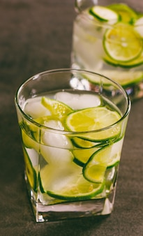 A refreshing cocktail with green lemon and ice close up, toning