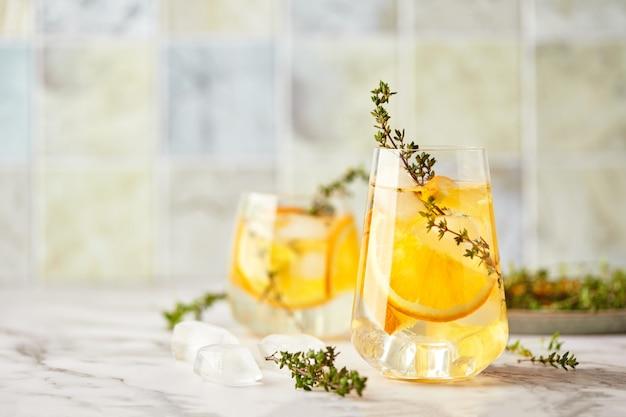 アイスオレンジとタイムの爽やかな夏のさわやかな夏の自家製アルコールまたはノンアルコールカクテルまたはモクテルまたはデトックス注入フレーバーウォーター