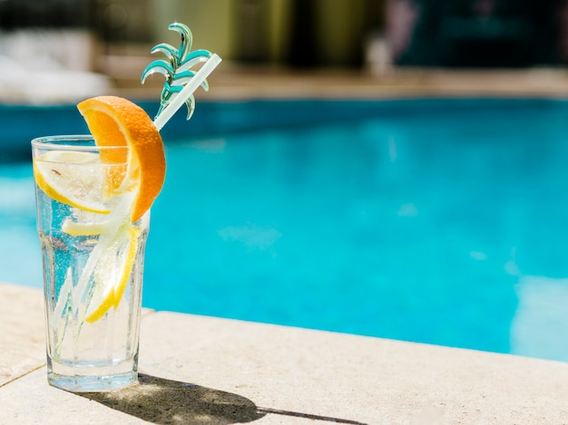 Refreshing cocktail with orange and lemon near pool