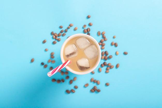 파란색 배경에 유리와 커피 곡물에 우유와 얼음으로 상쾌한 커피. 개념 여름, 얼음, 상쾌한 칵테일, 갈증. 평평한 평면도, 평면도