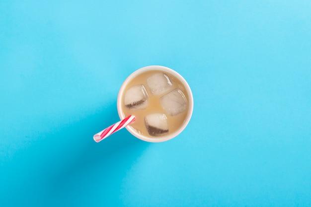 파란색 배경에 유리에 우유와 얼음으로 상쾌한 커피. 개념 여름, 얼음, 상쾌한 칵테일, 갈증. 평평한 평면도, 평면도