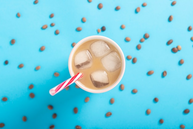 Refreshing coffee with milk and ice in a glass and coffee grains on a blue background. concept summer, ice, refreshing cocktail, thirst. flat lay, top view