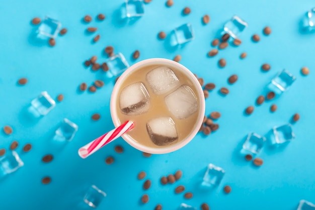 Refreshing coffee with milk and ice in a glass, ice cubes and coffee grains on a blue background. concept summer, ice, refreshing cocktail, thirst. flat lay, top view