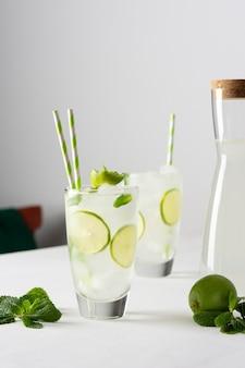 Освежающие холодные напитки с лаймом и мятой, стаканы с лимонадом и льдом и соломкой, кувшин с напитком на белом фоне