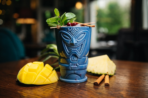 Освежающий холодный коктейль tiki drink с ананасом, манго, мятой и корицей