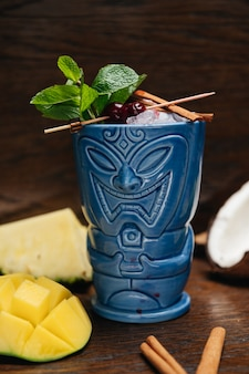 Refreshing cold tiki drink cocktail with pineapple mango mint and cinnamon