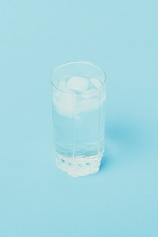 Refreshing cold water with ice in a glass on a blue surface.