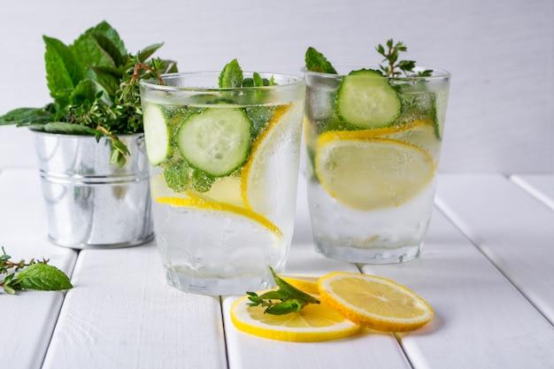 상쾌한 오이 칵테일, 레모네이드, 흰색 표면에 안경에 물 해독 여름 음료입니다.