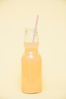 Refreshing drink in bottle with straw