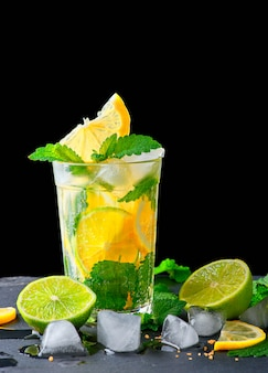 Refreshing drink lemonade with lemons, mint leaves, ice cubes and lime in a glass on a black background, copy space