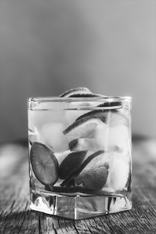 Refreshing drink with green lemon and ice close up, black and white