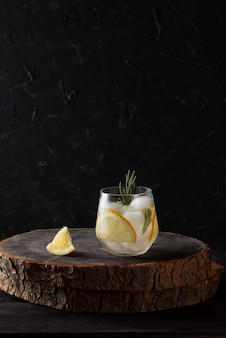Refreshing drink with lemon rosemary and ice on dark wooden background