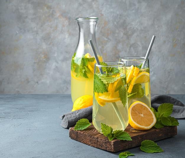 Освежающий напиток с мятой на сером фоне. лимонад в двух стаканах с трубочкой.