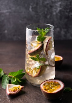 Refreshing drink with passion fruit. cocktail with tropical fruit on a dark background. with green mint leaves. vertical position