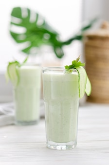 Refreshing fermented milk drink with cucumber and herbs. two with such a cocktail in a light interior on a white table.