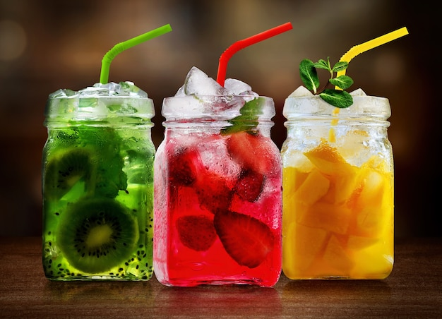 Refreshing fruits cocktails in glass jars on wooden table