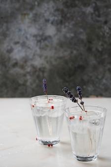 大理石の机の上にハーブ、スパイス、氷を添えたさわやかなジントニックカクテル。セレクティブフォーカス