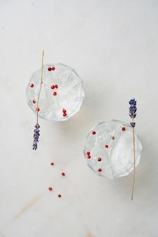 大理石の机の上にハーブ、スパイス、氷を添えたさわやかなジントニックカクテル。上面図