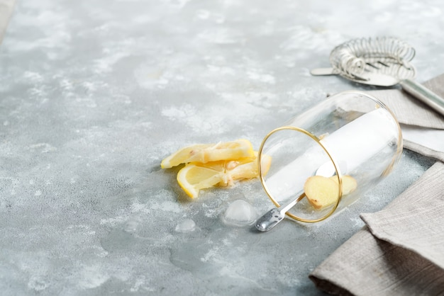 Refreshing ginger in a glass with drop water on a marble grey table.