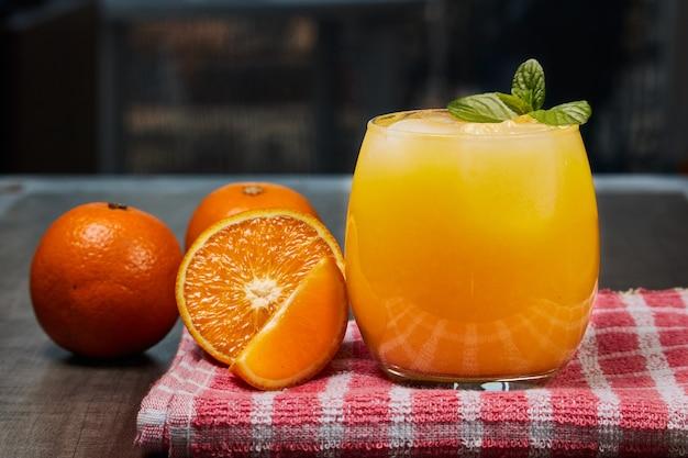 어두운 배경에 나무 테이블에 신선한 오렌지 주스, 얼음, 오렌지와 상쾌한 유리