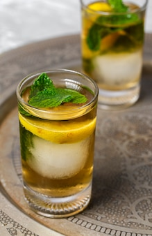 Refreshing glasses of tea with ice, mint and lemon wedges