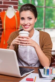 Освежая ее разум. веселый молодой модельер держит чашку с горячим напитком и улыбается, сидя на своем рабочем месте и с манекеном, стоящим на заднем плане