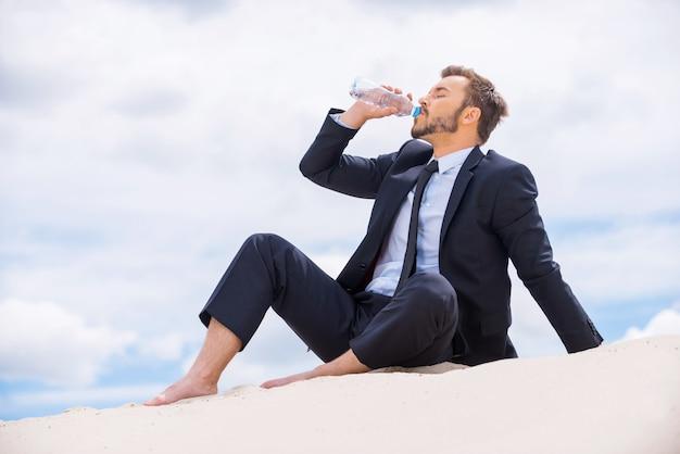 Освежая его разум. молодой бизнесмен пьет воду, сидя на вершине песчаной дюны