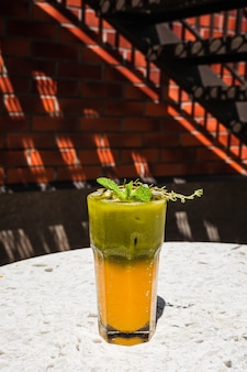 ミントとタイムを添えたハイボールグラスにオレンジジュースを添えたさわやかなアイス抹茶トニック