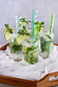 Освежающая вода с добавлением огурца, мяты и лайма. летом пейте коктейль-лимонад. концепция здорового напитка и детоксикации