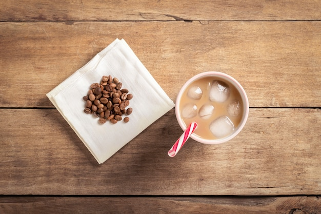 Refreshing and invigorating iced coffee in a glass and coffee grains on a wooden background. concept coffee shop, quenching thirst, summer. flat lay, top view