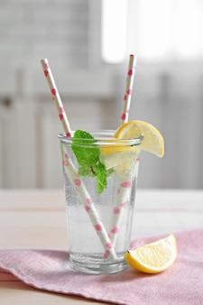 귀여운 냅킨에 짚으로 유리에 상쾌한 레몬 물