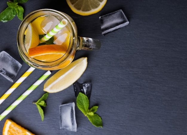 Refreshing lemonade in a jar on black background, top view