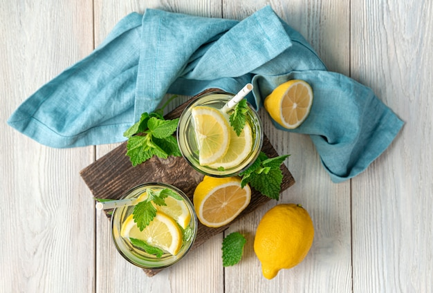 Refreshing lemonade and lemons with mint on a white background. top view, horizontal.