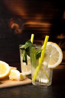 Limonata rinfrescante fatta di limoni freschi su fondo in legno vintage