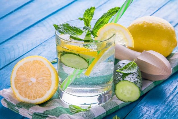 Освежающий лимонад из лимона, огурца, лайма и мяты на синем фоне. летний напиток. здоровые органические напитки