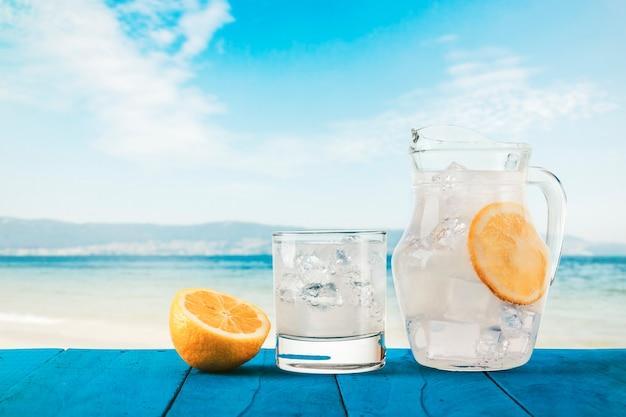Освежающий лимонад на синем деревенском деревянном столе на тропическом пляже