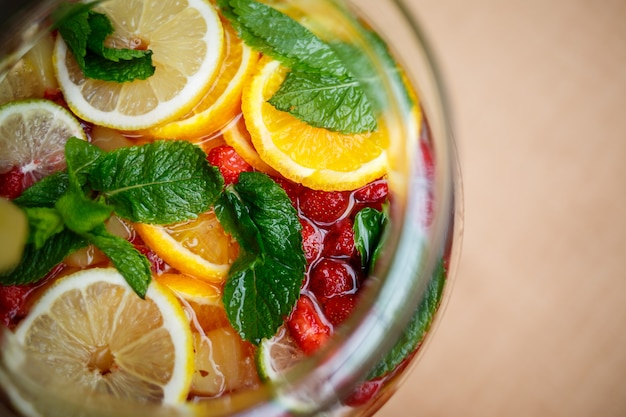 Refreshing lemonade with fresh fruit orange lemon cherry and mint leaves. delicious non-alcoholic fruit cocktail in a jug